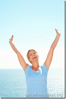 Excited middle aged woman with hands raised , outdoors